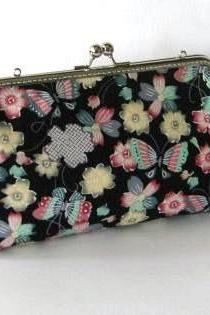 Butterflies and flowers on black clutch frame bag with removable strap
