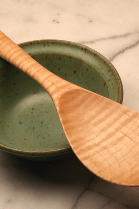 Hand carved wooden spoon rice spoon for serving sticky rice out of a rice cooker.