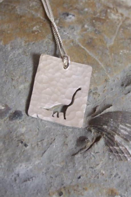 Silver Dinosaur pendant: A textured sterling silver pendant showing a silhouette of long necked Dinosaur.
