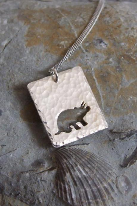 Silver Triceratops pendant: A textured sterling silver pendant showing a silhouette of Triceratops Dinosaur.