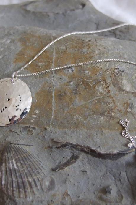 Silver Orion pendant: The constellation of Orion the hunter with his bow and arm on a domed sterling silver disc.