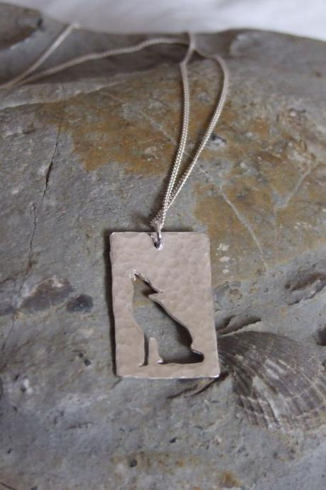 Stylized Wolf Pendant: A Howling wolf silhouetted against a background of textured sterling silver