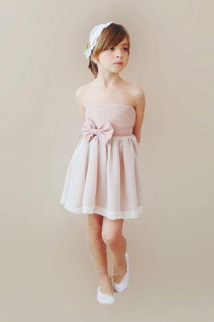 Pink mini custom flower girl dress for less. Strapless bodice features cute bow detail at side waist, flowing short skirt with ribbon hemline detail adds forcal point.