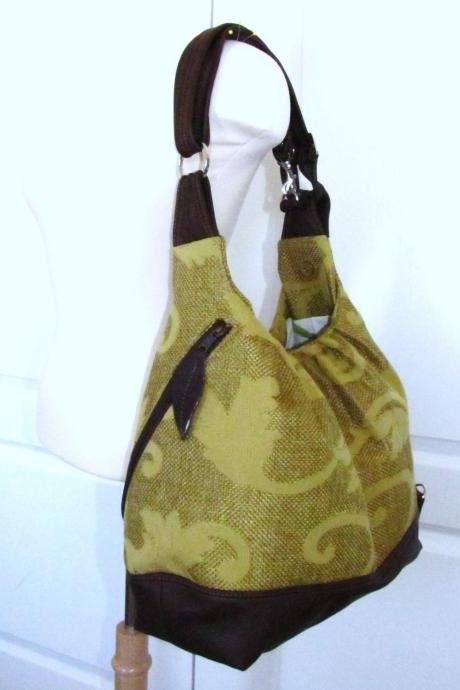 Green/gold vines canvas convertible bag with leather straps, bottom, and zipper top closure