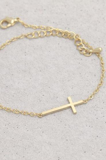 Sideways cross bracelet in gold